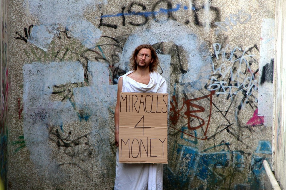Miracle Man standing with sign around his neck that reads 'Miracles 4 Money'